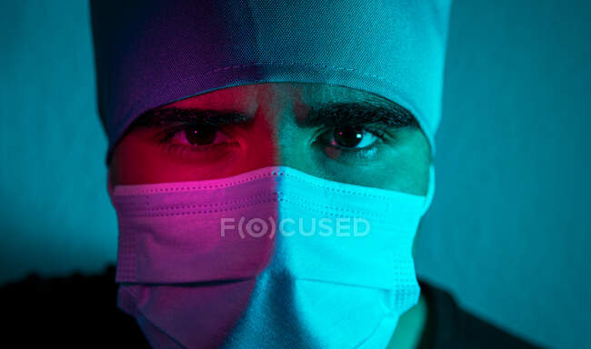 Closeup of male surgeon in medical mask looking at camera in dark room with blue and red neon light — Stock Photo