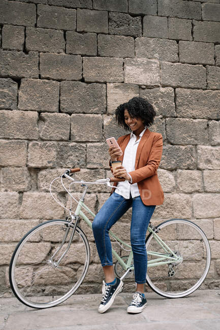 Delighted African American female standing near parked bike with takeaway drink and messaging on social media on smartphone on street — Stock Photo