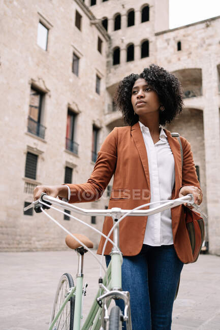 Dal basso della donna nera in stile smart casual passeggiando lungo la strada con la bici e guardando altrove — Foto stock