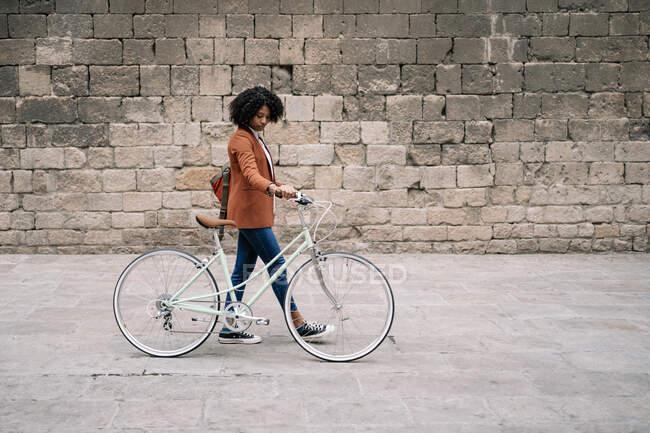 Бічний погляд на чорну жінку в розумному повсякденному стилі йде по вулиці з велосипедом і дивиться вниз — стокове фото