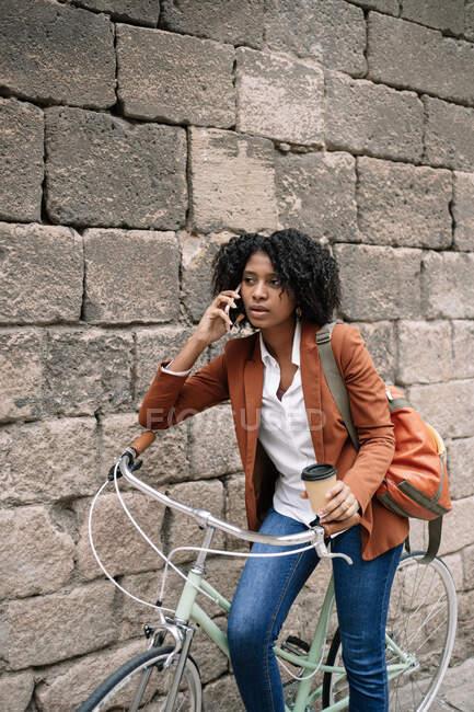 Entzückte Afroamerikanerin steht neben geparktem Fahrrad mit Imbissgetränk und Telefongespräch auf der Straße — Stockfoto