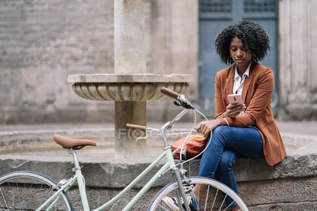 Young African American female in stylish casual outfit browsing mobile phone while sitting near bicycle on old stone fountain border in city — Stock Photo