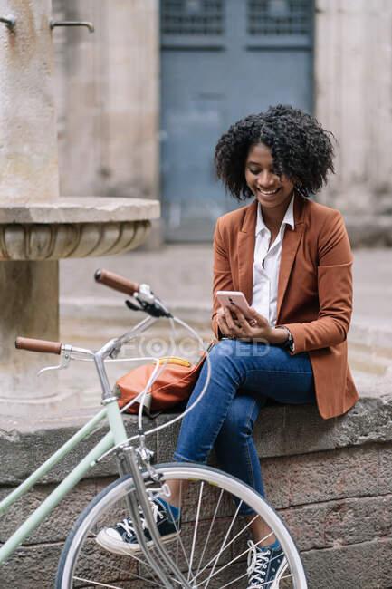 Jeune femme afro-américaine en tenue décontractée élégante navigation téléphone mobile tout en étant assis près de vélo sur la vieille fontaine de pierre frontière en ville — Photo de stock