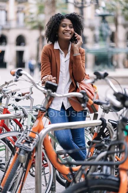 Femme afro-américaine souriante debout près du vélo garé et parlant sur un téléphone portable en ville tout en regardant loin — Photo de stock