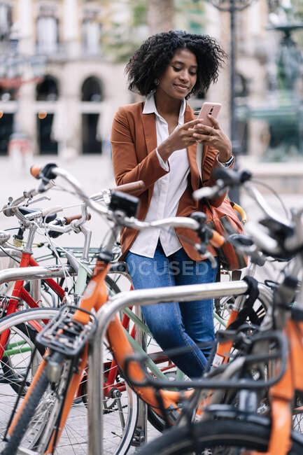 Улыбающаяся афроамериканка, стоящая рядом с припаркованным велосипедом и просматривающая мобильный телефон в городе — стоковое фото