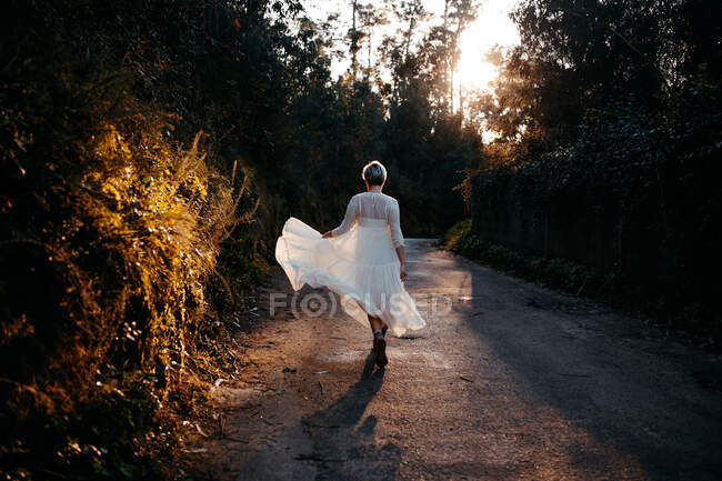 Full body back view of anonymous female wearing white dress walking on rural road among green trees in nature on evening time — Stock Photo