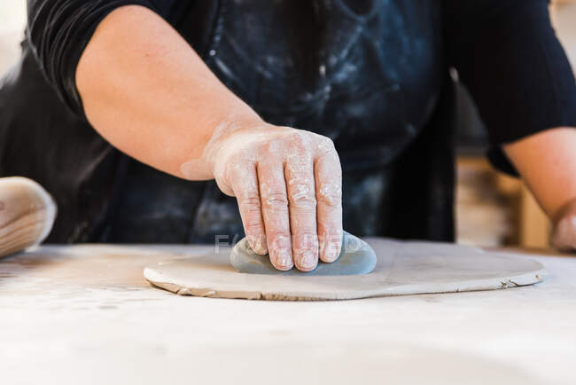 Crop unrecognizable artist cutting out circles from clay while working in workshop — стоковое фото