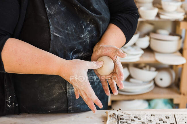 Crop anonymous master in black dirty apron standing in workshop and shaping piece of clay in hands near table with tools for handicraft — стоковое фото