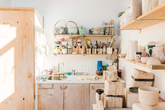 Studio with wooden shelves with different instruments for pottery and utensil near sink in daylight — стоковое фото