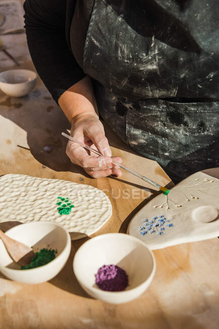 Crop anonymous female artisan in dirty black apron using paintbrush for painting ceramic palette on table near bowls with pigment in bright workshop — Stock Photo