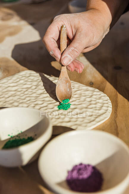 Crop unrecognizable person putting green ceramic pigment with wooden spoon on uneven clay board for filling in drawing near bowls with powder on table in light workshop — Stock Photo