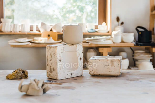 Light studio with ceramic pots on surface near shelf with handmade clayware — стоковое фото