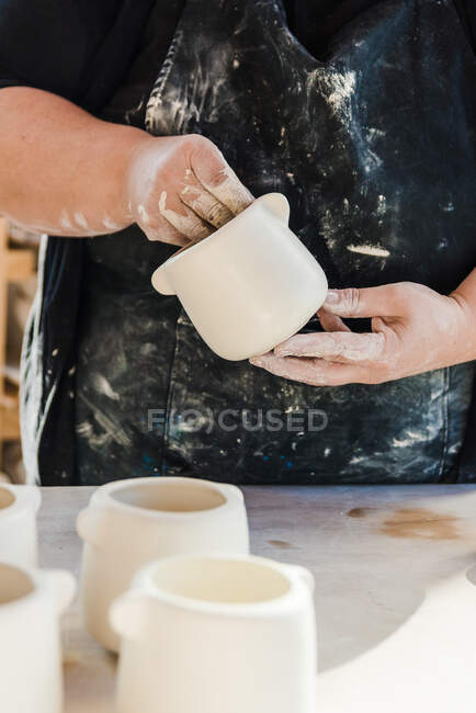 Cropped unrecognizable adult female artisan in dirty apron and black clothes standing in light studio and holding handmade ceramic pot near clayware — Stock Photo