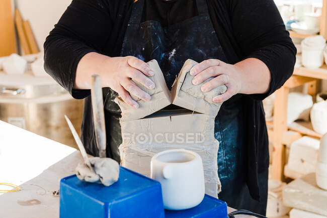 Crop unrecognizable female artisan in apron cutting clay while preparing for sculpturing in workshop — Stock Photo