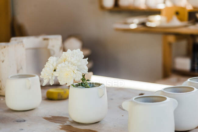 Set of white ceramic cups with flowers placed on counter in light studio near objects for handicraft — стоковое фото