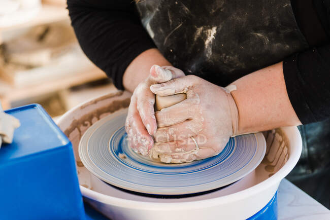 Crop anonymous female artisan in apron modeling clay pot on throwing wheel — Stockfoto