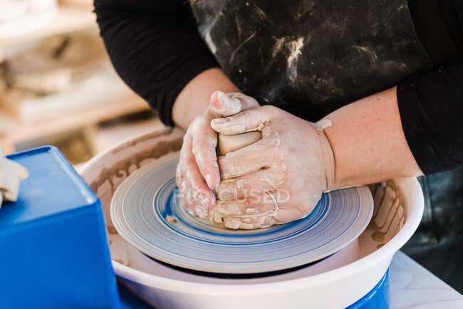 Жінка - ремісниця у фартусі, що виготовляє глиняний горщик на колесах. — стокове фото