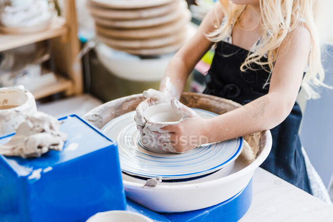 Crop unrecognizable little girl in black apron standing near pottery wheel while shaping clay pot in light workshop — Stock Photo