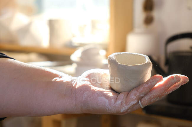 Cropped unrecognizable adult female artisan standing in light studio and holding fresh handmade ceramic pot — Stock Photo