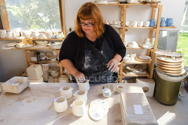 Adult female artisan in dirty apron and black clothes standing in light studio with handmade ceramic pots near clayware — Stock Photo