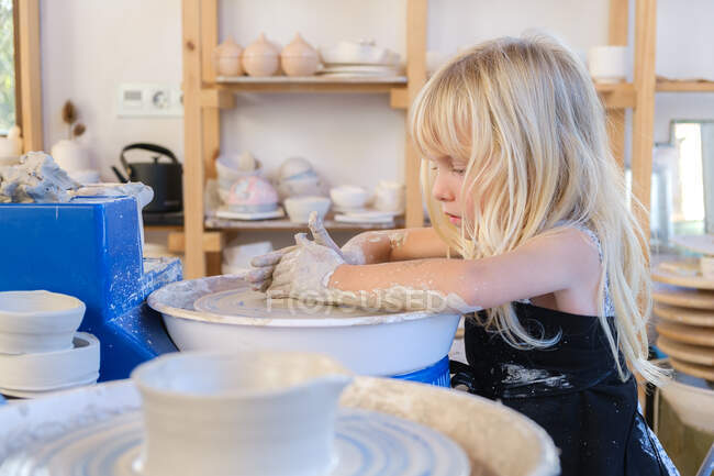 Side view of little girl in black apron standing near pottery wheel while shaping clay pot in light workshop — Stock Photo