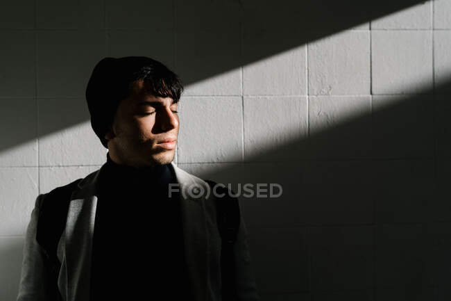 Tranquil male student with backpack standing with closed eyes near wall lit by sunlight — Stock Photo
