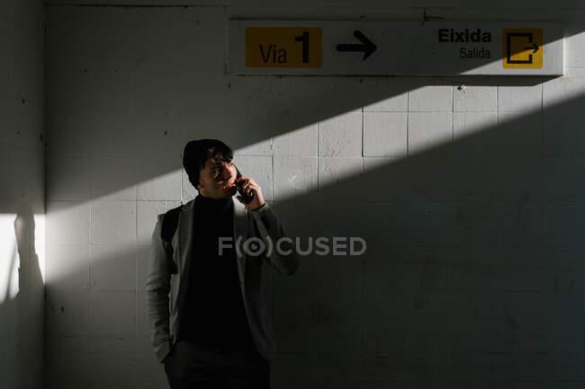 Elegante estudiante masculino de pie en la clandestinidad y hablando por teléfono móvil mientras mira hacia otro lado — Stock Photo