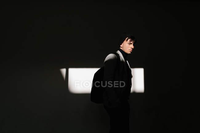 Зворотний погляд на спокійного студента з рюкзаком, що стоїть біля стіни освітленої сонячним світлом. — стокове фото