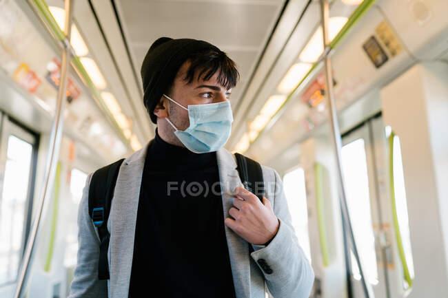 Молодий студент на обличчі й рюкзак їде сучасним поїздом під час поїздки до університету під час пандемії коронавірусу. — стокове фото