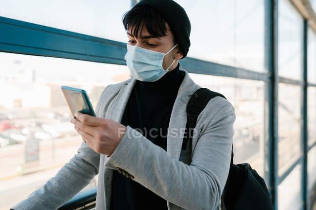 Чоловічий учень у масці і рюкзак, що йде коридором на залізничній станції і дивиться смартфон. — стокове фото