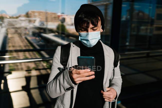 Чоловічий учень в масці і рюкзак стоїть біля скляного дзеркала вздовж коридору на залізничній станції і переглядає смартфон — стокове фото