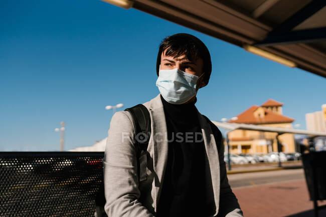 Studente di sesso maschile in maschera protettiva seduto sul marciapiede alla stazione ferroviaria in attesa di treno e guardando altrove — Foto stock