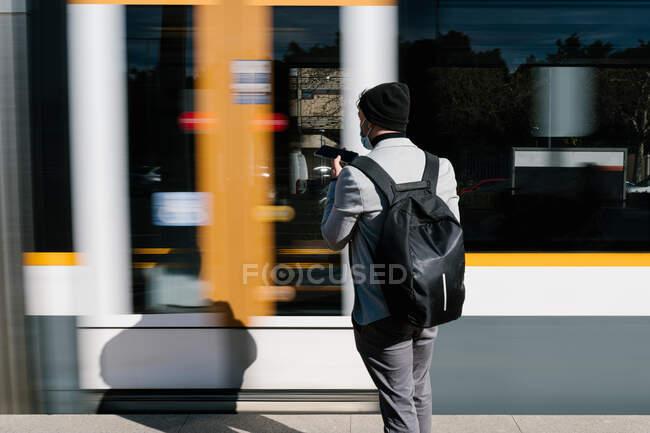 Visão traseira de estudante do sexo masculino irreconhecível com mochila em pé na plataforma na estação ferroviária perto de trem de equitação rápida e gravação de mensagem de áudio no smartphone — Fotografia de Stock