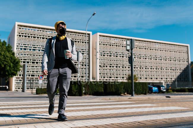 Baixo ângulo de estudante do sexo masculino em máscara e com café para ir cruzar estrada na cidade enquanto viaja para a universidade e olhando para longe — Fotografia de Stock