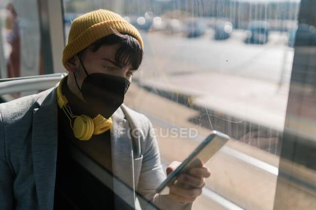 Студент-мужчина в разноцветной шапочке и маске сидит возле окон современного поезда и просматривает смартфон во время пандемии коронавируса — стоковое фото