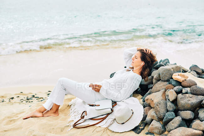 Side view of tranquil female lying on beach near sea and enjoying music in earphones with closed eyes — стоковое фото