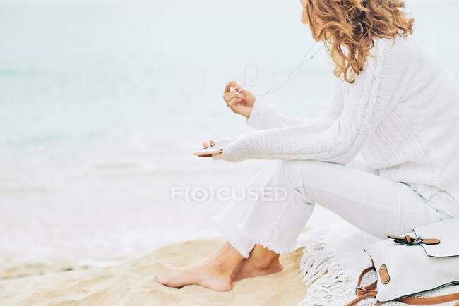 Side view of tranquil female sitting on beach near sea and enjoying music on earphones and using mobile — Stock Photo
