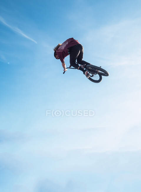 From below side view of unrecognizable male biker jumping on trial bicycle in air under blue cloudy sky — Foto stock