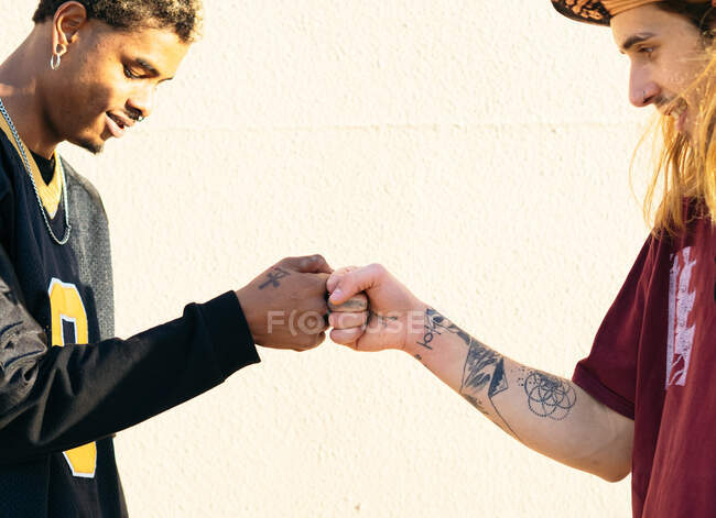 Side view of crop young multiracial hipster men in cool outfit with piercings and tattoos greeting each other on light background — стоковое фото
