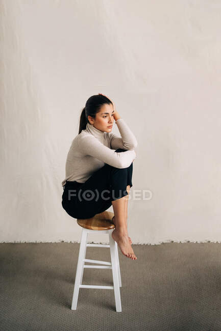 Вид сбоку на молодую несчастную босиком женщину в повседневной одежде, сидящую на стуле и смотрящую в сторону — стоковое фото