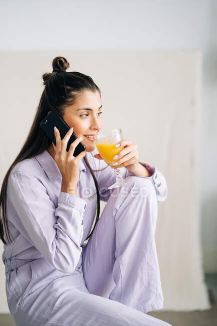 Jeune femme amicale avec un verre de jus d'orange parlant sur un téléphone portable à la maison — Photo de stock