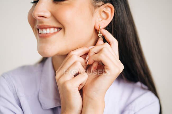 Ritaglia giovane contenuto femminile con sorriso dentato e gli occhi chiusi mostrando orecchino durante il giorno — Foto stock