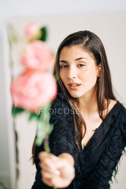 Young sensual female in black clothes with blossoming flower looking at camera — Stock Photo