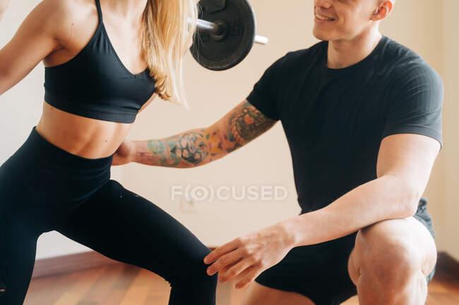 Сильная женщина в черной активной одежде делает барбекю обратно приседания упражнения с помощью личного инструктора мужчина во время тренировки на дому — стоковое фото