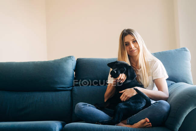 Full body of barefoot cheerful female owner looking at camera while sitting on sofa crossed legged with black dog at home — Stock Photo