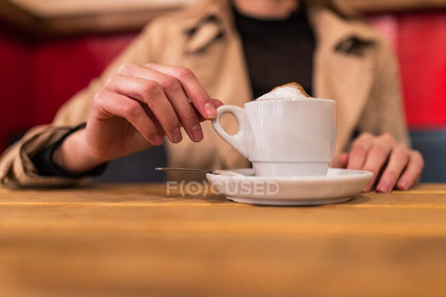 Unrecognizable crop female sitting at table with mug of aromatic cappuccino and enjoying weekend in coffee shop — Stock Photo