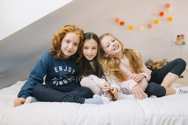 Веселі діти, які відпочивають на ліжку у спальні під час вихідних. — стокове фото