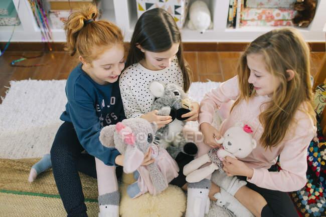 Зверху гарненькі дівчатка в повсякденному одязі сидять на килимі і бавляться іграшками, проводячи разом час. — стокове фото