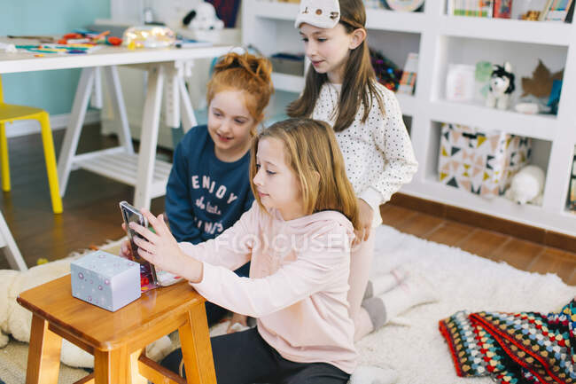 From above happy little girls in casual clothes sitting in playroom against mobile phone while filming video of dance — Stock Photo