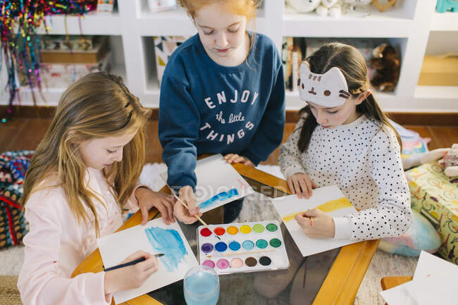 Cute adorable girls sitting at table with sheets of paper and watercolor while drawing pictures together — Stock Photo